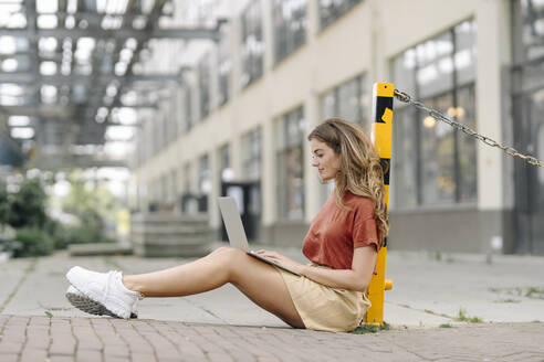 Young brunette woman using laptop, sitting on the ground - KNSF06950