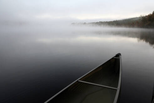 A sleek canoe tied to a dock on a tranquil pond in Maine. - CAVF70488