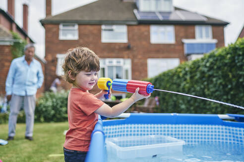 Boy playing with water gun by pool - CUF53851