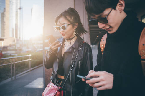 Young couple using mobile phone while walking on street, Milan, Italy - CUF54073