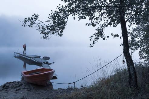 Man on pier in lake in morning fog - JOHF05025