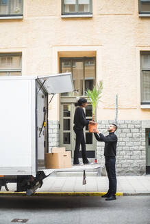 Male and female movers unloading potted plant from truck on street in city - MASF15277