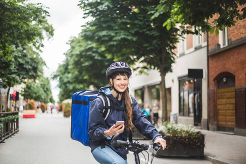 Portrait of smiling food delivery woman with bicycle on city street - MASF15283