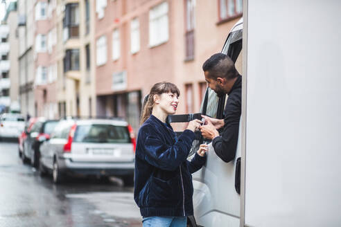 Young woman signing on smart phone being held by male mover in truck - MASF15301