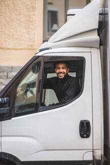 Portrait of smiling male mover driving truck - MASF15304