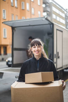 Portrait of smiling female mover carrying cardboard boxes - MASF15313