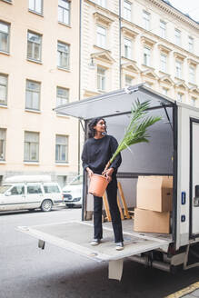 Female mover unloading potted plant from truck on street in city - MASF15316