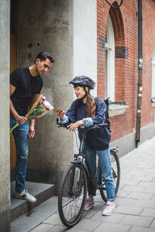 Delivery woman showing mobile phone to male customer while delivering bouquet - MASF15334