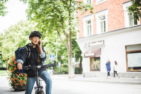 Food delivery woman talking on smart phone at street in city - MASF15343