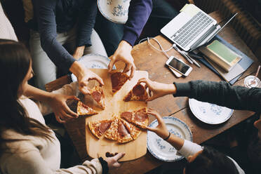 High angle view of friends taking slices of pizza at dining table - MASF15451