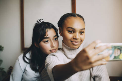 Teenage girls taking selfie with smartphone at home - MASF15460