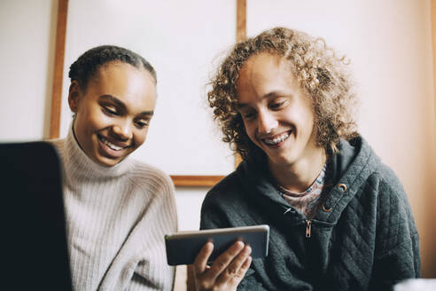 Male and female teenagers smiling while looking at smart phone in room - MASF15463