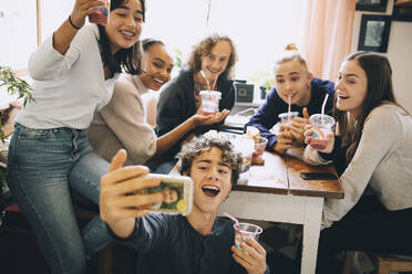 Teenage boy taking selfie with friends on smart phone while drinking smoothie at home - MASF15466