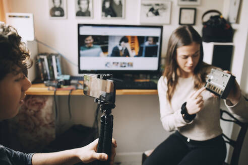 Teenage boy filming friend using sound mixer on monopod while sitting at home - MASF15493