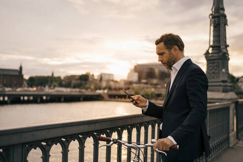 Businessman using mobile phone while standing with bicycle on bridge in city during sunset - MASF15508