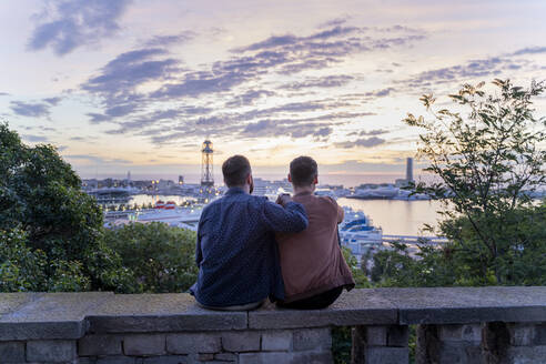 Gay couple on lookout above the city with view to the port, Barcelona, Spain - AFVF04417