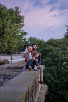 Smiling gay couple sitting on a wall at sunset - AFVF04420