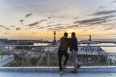 Gay couple on lookout above the city with view to the port, Barcelona, Spain - AFVF04429