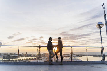 Gay couple on lookout above the city with view to the port, Barcelona, Spain - AFVF04435