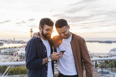 Gay couple using cell phone on lookout above the city with view to the port, Barcelona, Spain - AFVF04438