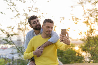Affectionate gay couple taking a selfie outdoors at sunset - AFVF04444