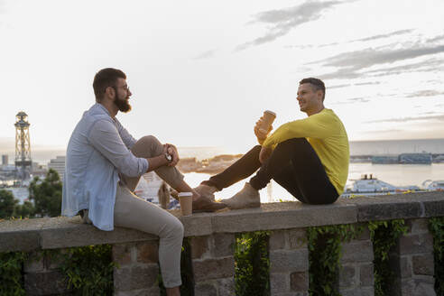 Two men sitting on a wall on lookout above the city with view to the port, Barcelona, Spain - AFVF04447