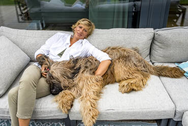 Woman relaxing with dog on terrace at home - BFRF02147