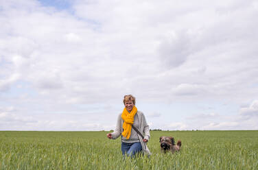 Happy woman going walkies with dog in a field - BFRF02150