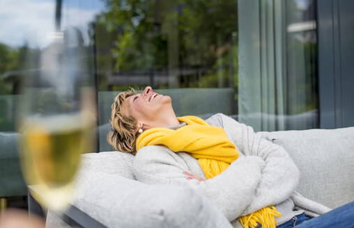 Happy woman relaxing on terrace at home - BFRF02153