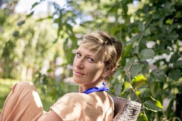 Portrait of woman relaxing in garden - BFRF02156