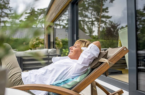 Woman relaxing in deckchair on terrace at home - BFRF02159