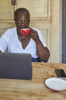 Senior woman sitting at kitchen table using laptop and drinking from cup - VEGF01084