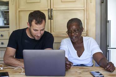 Senior woman and man sitting at kitchen table sharing laptop - VEGF01087