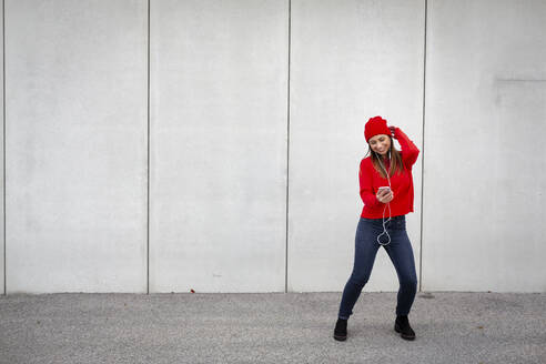 Woman wearing red pullover and wolly hat and dancing in front of a wall - HMEF00692
