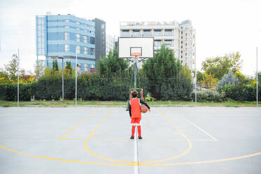 Boy standing with basketball on outdoor court - JCMF00334