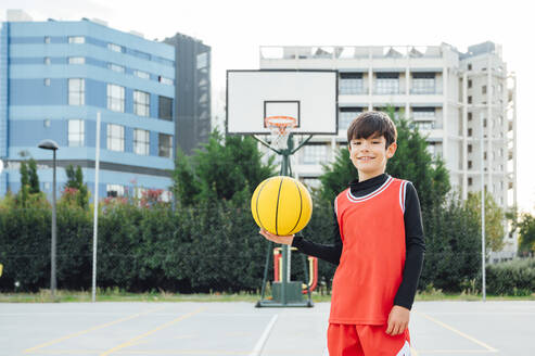 Portrait of smiling boy with basketball on outdoor court - JCMF00337