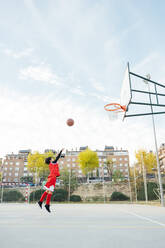 Boy playing basketball on outdoor court - JCMF00340
