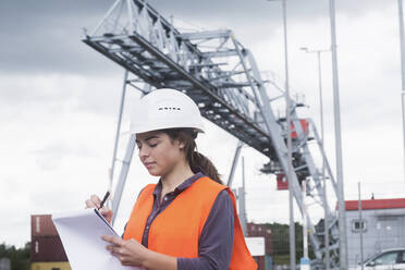 Female worker with clipboard taking notes on industrial site - SGF02498