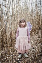 Portrait of happy little girl in nature dressed up as a butterfly - RORF01965