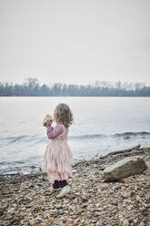 Back view of little girl wearing pink fancy dress costume standing at riverside holding a stone - RORF01974