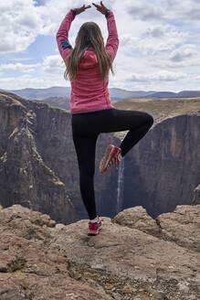 Woman balancing on top of a hill at Maletsunyane Falls enjoying the view, Lesotho - VEGF01169
