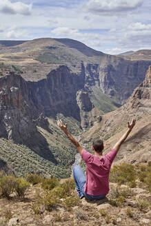 Man sitting on top of a hill at Maletsunyane Falls enjoying the view, Lesotho - VEGF01172