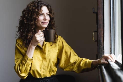 Woman looking out of window with coffee cup - FMOF00841