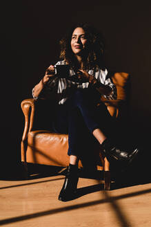 Woman sitting in leather armchair with coffee cup - FMOF00850