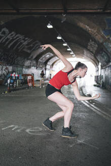 Young woman dancing at an underpass in the city - FBAF01094