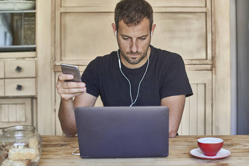 Man working from home, sitting at kitchen table, using laptop and smartphone - VEGF01208