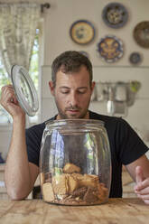 Man sitting in kitchen, looking in cookie jar - VEGF01211