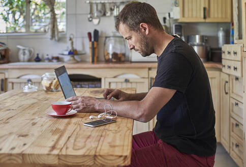 Man working from home, sitting at kitchen table, using laptop and smartphone - VEGF01214