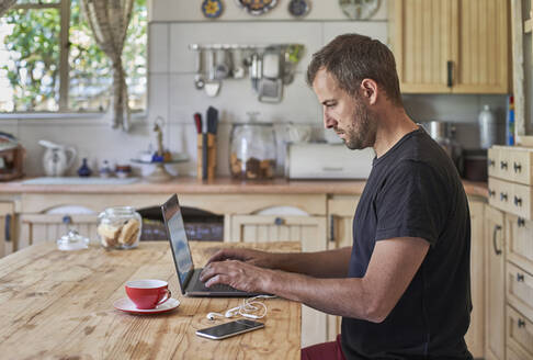Man working from home, sitting at kitchen table, using laptop and smartphone - VEGF01217
