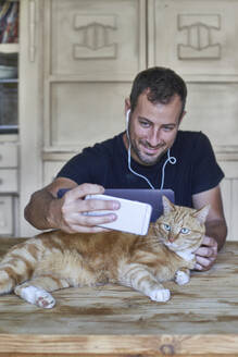 Man sitting at table, taking picture of his ginger cat with smartphone - VEGF01223